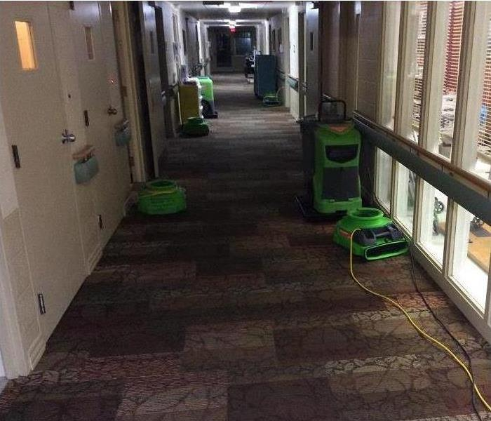 SERVPRO equipment drying out water from carpeted hallway